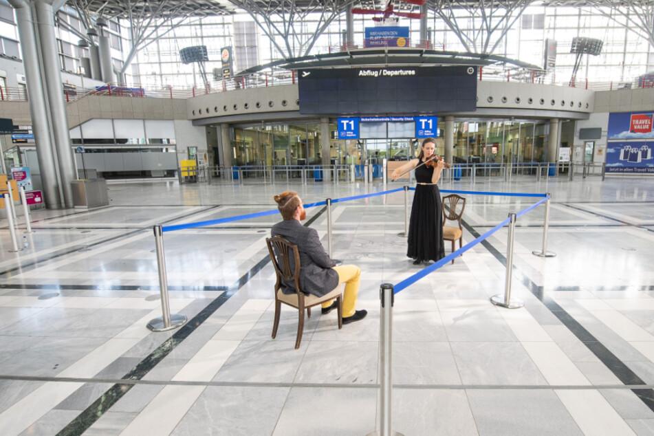 Elena Graf, 1. Konzertmeisterin der Staatsoper Stuttgart, spielt während des Drehs eines Trailers für Eins-zu-Eins-Konzerte der Oper Stuttgart im Terminal 1 des Flughafens Stuttgart für einen Zuhörer auf der Violine.