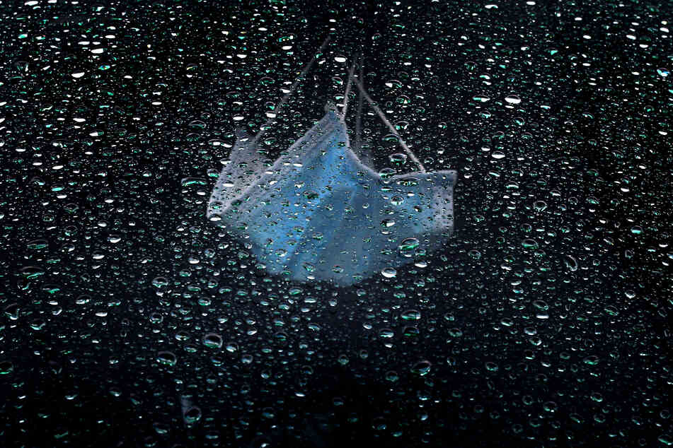 Ein medizinischer Mundnasenschutz hängt am Rückspiegel eines im Regen parkenden Autos.