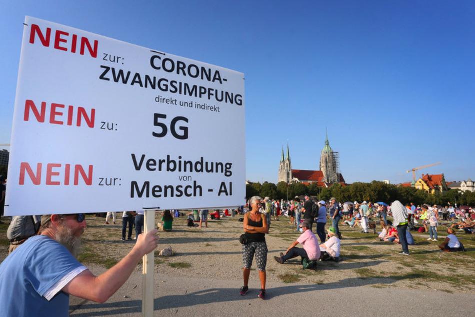 """Auf der Theresienwiese hält ein Mann ein Plakat mit der Aufschrift """"Nein zu Corona-Zwangsimpfung Nein zu G5 Nein zur Verbindung von Mensch -Al""""."""