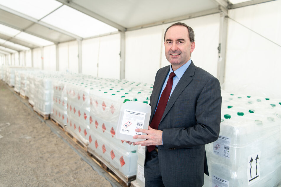 Hubert Aiwanger, Wirtschaftsminister und Landesvorsitzender der Freien Wähler in Bayern, hält in einem Zelt einen Kanister mit Handdesinfektionsmittel in den Händen, während hinter ihm Paletten mit Hunderten weiteren Kanistern zu sehen sind.