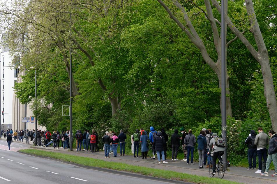 Entlang der Inneren Kanalstraße in Köln-Ehrenfeld hat sich eine lange Schlange von Wartenden gebildet.