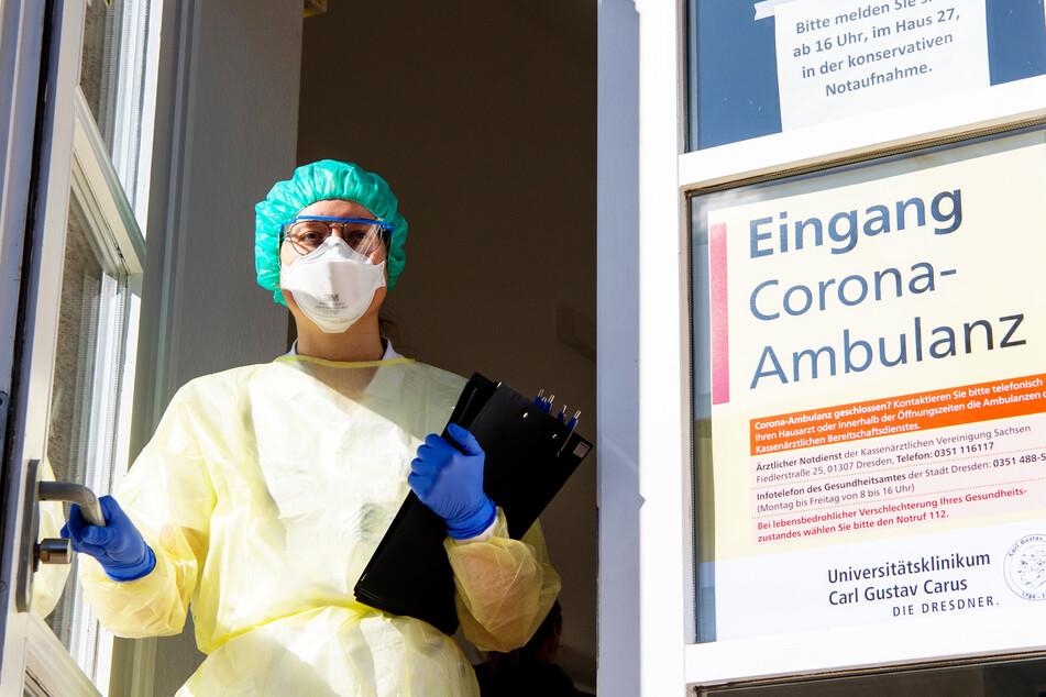 Eine Infektiologin der Klinischen Infektiologie am Dresdner Uniklinikum steht am Eingang der Corona-Ambulanz.