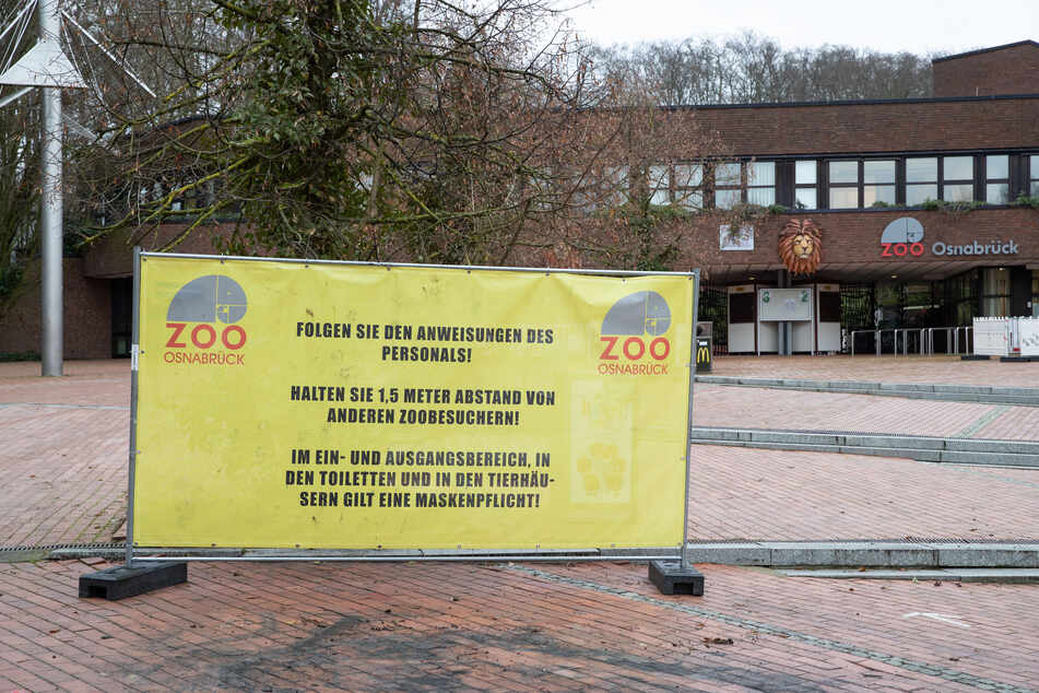 Auf einem Plakat wird um Abstand zu anderen Zoobesuchern gebeten.