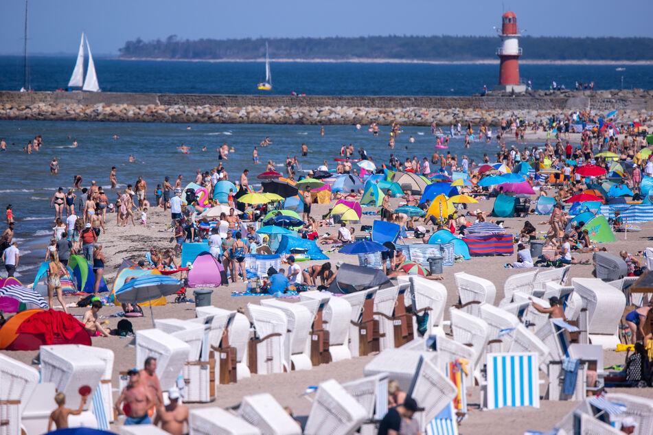 Badegäste am Strand in Warnemünde. Bei sommerlichen Temperaturen und Sonnenschein zieht es Urlauber und Einwohner an die Strände entlang der Ostsee.