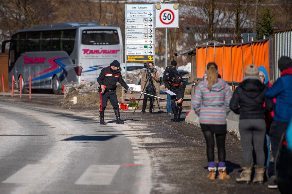 Zwei Einsatzkräfte der Carabinieri rekonstruieren im Februar den Unfallhergang, während Teilnehmer einer Reisegruppe zusehen.