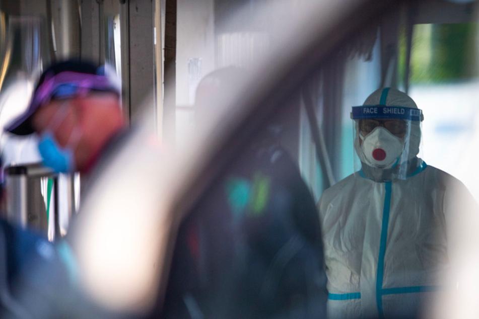 Eine Mitarbeiterin des Corona-Testzentrums steht neben Personen, die sich für einen Corona-Test registrieren.