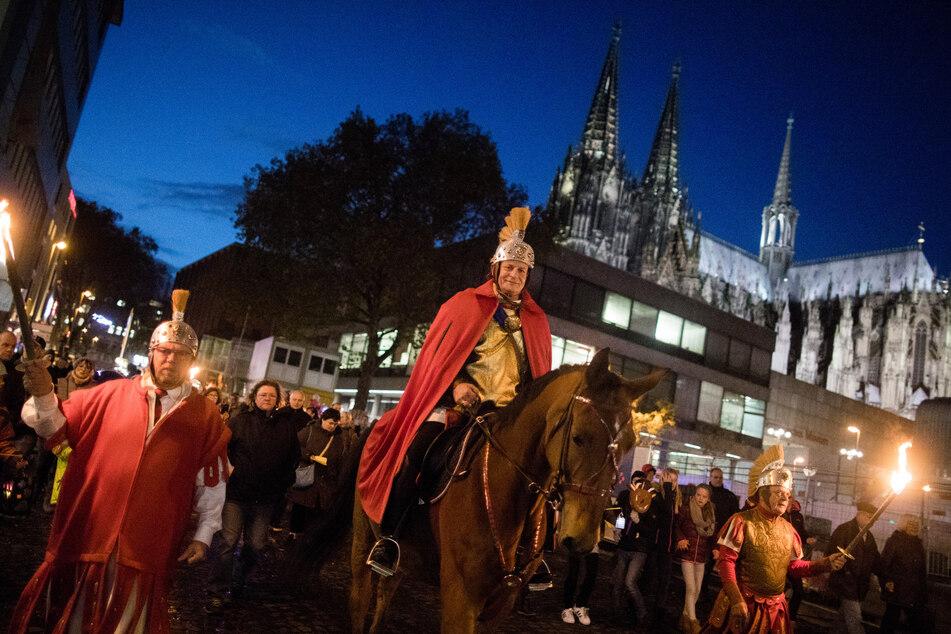 """Der """"Heilige Sankt Martin"""" reitet bei einem Martinszug am Dom vorbei. Martinsumzüge sind in diesem Jahr in Nordrhein-Westfalen verboten (Archivbild)."""