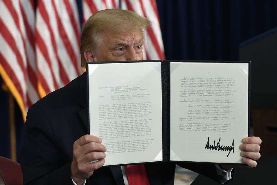 US-Präsident Donald Trump hält im Trump National Golf Club eine unterzeichnete Verfügung in der Hand.