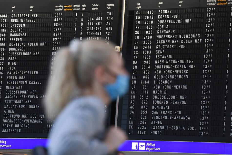 Eine Frau, die einen Mundschutz trägt, steht im Terminal 1 des Frankfurter Flughafens in der Abflughalle vor einer großen Anzeigetafel. Am größten deutschen Airport öffnet nun das erste Corona-Testzentrum an einem Flughafen in Deutschland.