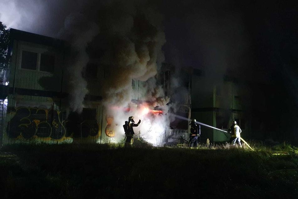 Feuerwehrleute löschen die brennende Flüchtlingsunterkunft.