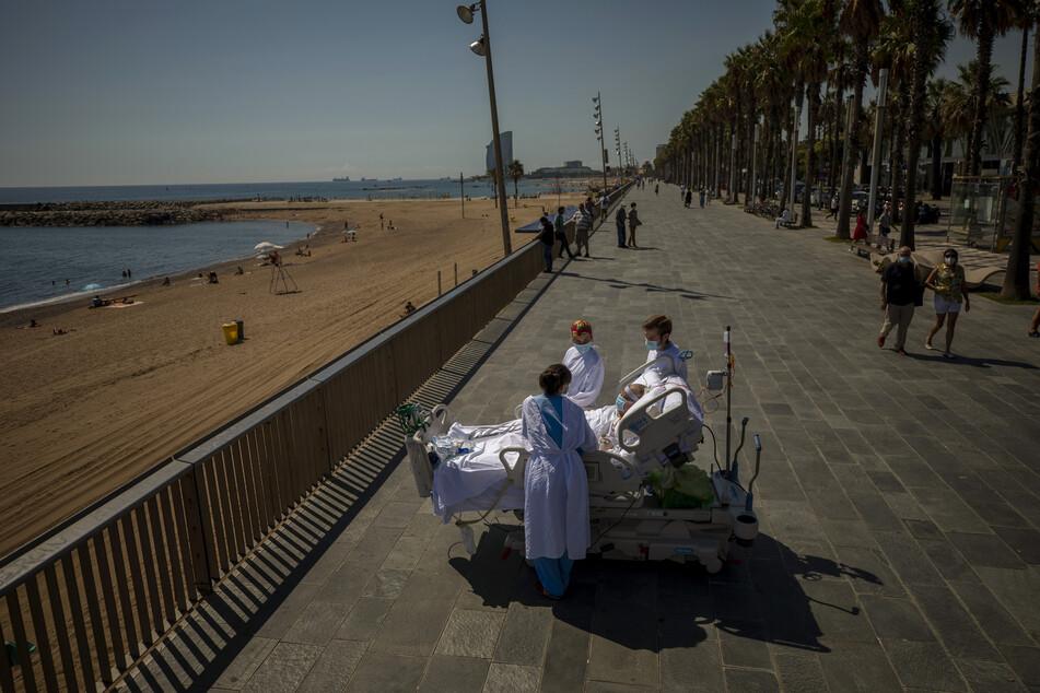 Francisco Espana, 60 Jahre alt, ist von Mitgliedern seines Ärzteteams umgeben, als er von einer Promenade neben dem Hospital del Mar in Barcelona auf das Mittelmeer blickt. Francisco verbrachte aufgrund einer Corona-Infektion 52 Tage auf der Intensivstation des Krankenhauses, doch am Freitag wurde ihm von seinen Ärzten erlaubt, im Rahmen seiner Genesungstherapie fast zehn Minuten am Meer zu verbringen.