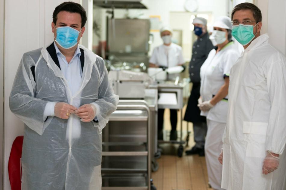 Bundesarbeitsminister Hubertus Heil (l) und Potsdams Oberbürgermeister Mike Schubert (beide SPD) tragen beim Besichtigen der Küche Bisamkiez Handschuhe, Mundschutz und Schutzkleidung.