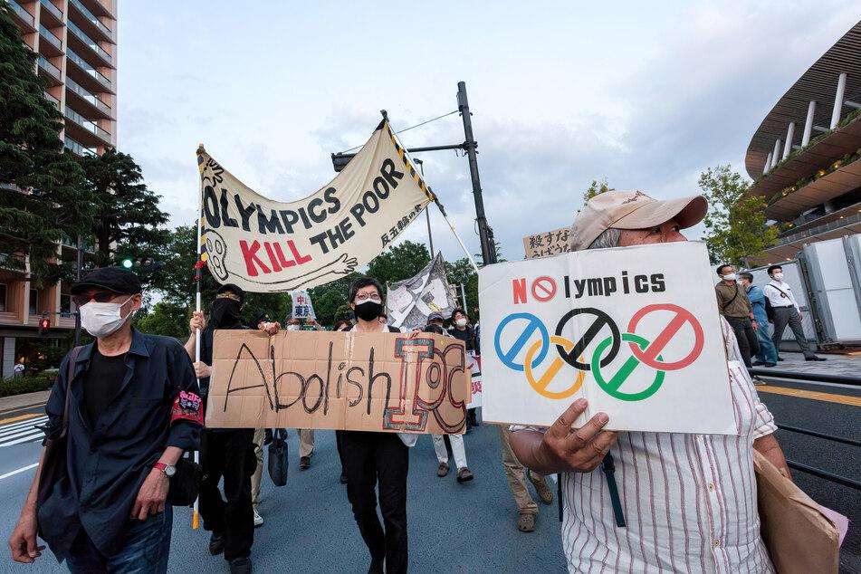 """Protestteilnehmer in Tokio halten Schilder mit der Aufschrift """"No Olympics"""" (Keine Olympischen Spiele) in die Höhe, während sie durch eine Straße gehen. Die Demonstranten sind aufgrund der Corona-Pandemie gegen die Austragung der Olympischen Spiele, die am 23. Juli in der japanischen Hauptstadt eröffnet werden sollen."""