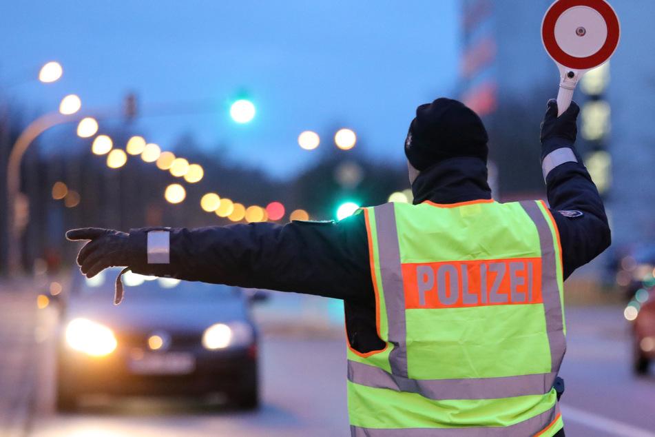 Ein Polizist winkt ein Auto für eine Verkehrskontrolle heraus. (Symbolfoto)