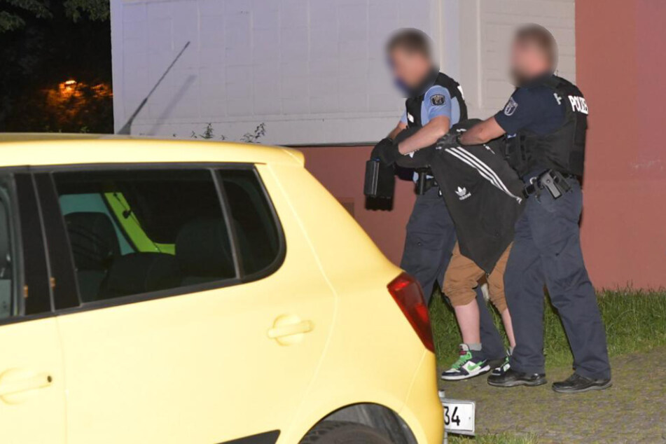 Polizisten führen einen der Verdächtigen ab.