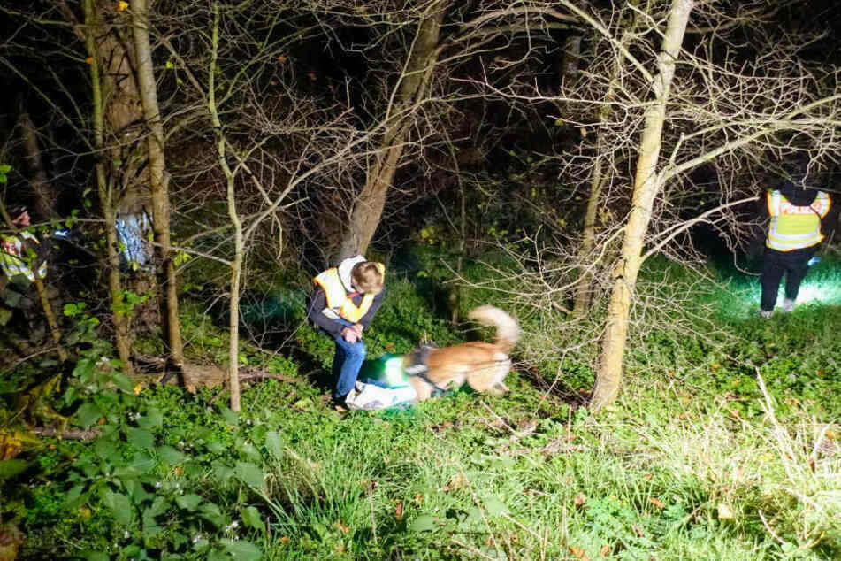 Polizeibeamte untersuchen mit einem Spürhund die Fundstelle.