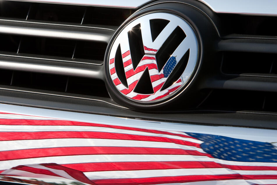 """Die US-Fahne spiegelt sich in Logo und Kühlergrill eines Volkswagen-Fahrzeugs. Volkswagen muss in der """"Dieselgate""""-Affäre weitere empfindliche Bußgelder in den USA fürchten. Ein Berufungsgericht entschied am Montag, dass trotz bereits geschlossener Vergleiche zusätzliche Strafen zweier Bezirke der Bundesstaaten Florida und Utah zulässig seien."""