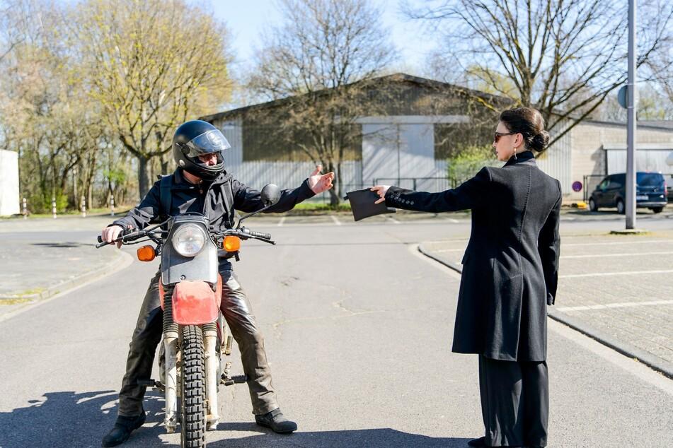 Simone übergibt einem unbekannten Biker eine Tasche mit Geld und Passfotos, die er ihr aus den Händen reißt und wegfährt.