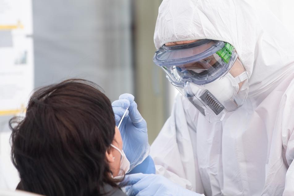 Ein Mitarbeiter des Deutschen Roten Kreuzes (DRK) macht in Schutzkleidung einen Corona-Test mittels Abstrichstäbchen bei einer Frau.