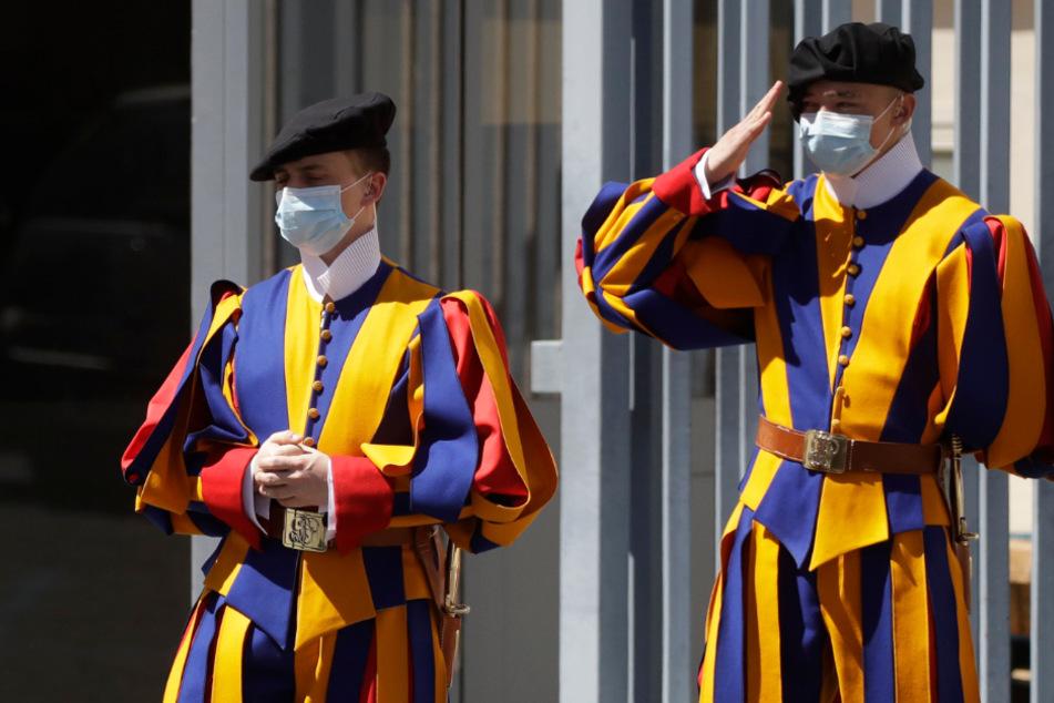 Zwei uniformierte Gardisten der Päpstlichen Schweizergarde stehen mit Mund-Nasen-Schutz im Mai 2020 am Eingang zum Vatikan.