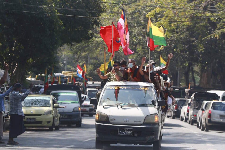 Religiös buddhistische und militärische Fahnen werden von Anhängern der Militärregierung, darunter buddhistische Mönche, auf einem Fahrzeug geschwenkt.
