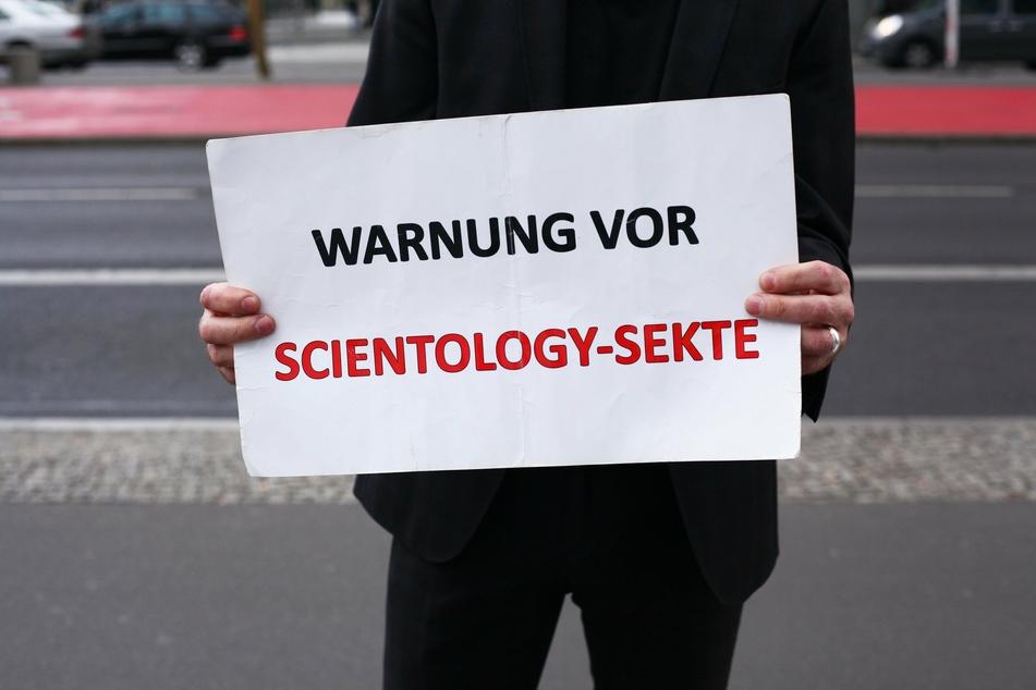 Ein Mann demonstriert am Rande einer Veranstaltung der Scientology-Sekte gegen die Organisation.