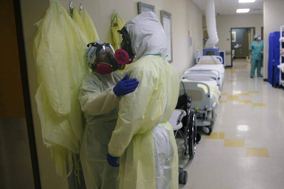 Medizinische Mitarbeiter von DHR Health in Schutzkleidung sprechen miteinander auf einem Flur einer Einrichtung in McAllen zur Betreuung von Covid-19-Patienten.