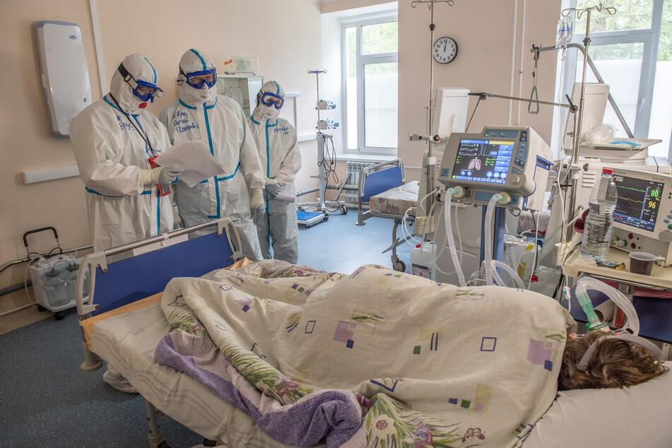 Medizinisches Personal in Schutzanzügen kümmert sich um einen Covid-19-Patienten. (Archivbild)