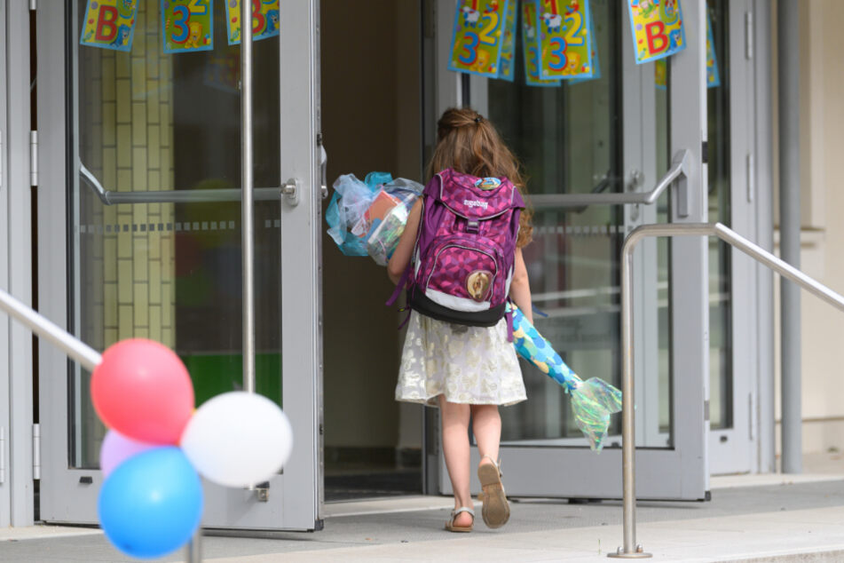 Die kleine Emma wartet nach der Schuleingangsfeier mit ihrer Zuckertüte in den Armen vor der Grundschule. In Sachsen haben am Samstag tausende Grundschüler vor dem Start in das erste Schuljahr ihre Einschulung gefeiert.