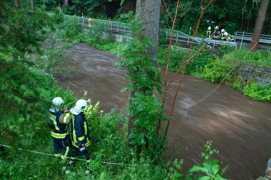 Die Feuerwehr kontrolliert den Steinbach und spannt Stahlseile über das Wasser, an denen sich der Vermisste notfalls festhalten könnte.
