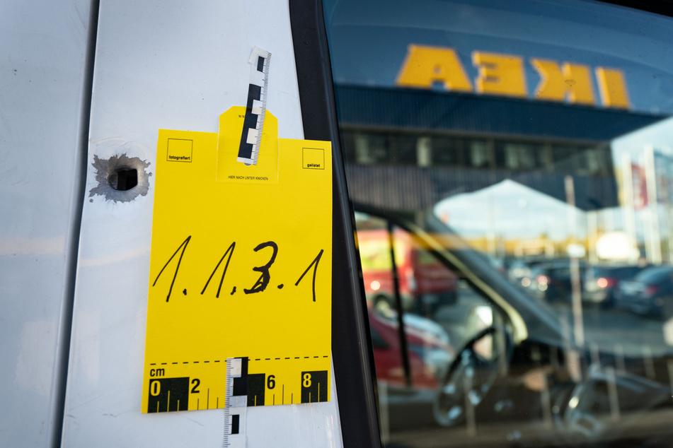 Vor einem Möbelhaus in Frankfurt am Main wurde 2019 ein Geldbote überfallen und angeschossen. Die Spurensicherung kennzeichnete das Einschussloch an dem Geldtransporter.