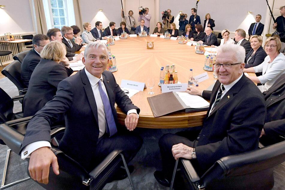 Der baden-württembergische Ministerpräsident Winfried Kretschmann (Bündnis 90/Die Grünen, r), und Innenminister Thomas Strobl (CDU, l) sitzen im Landtag von Baden-Württemberg im Kabinettssaal. (Archivbild)