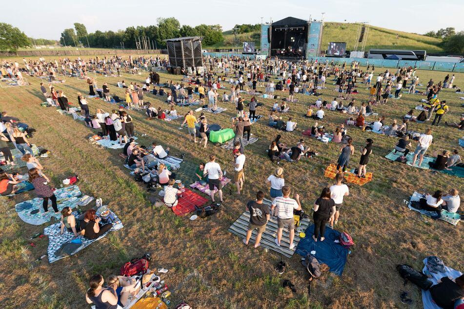 """Die Zuschauer stehen und sitzen während eines Konzerts der Band Meute, das in der Reihe """"Picknick-Konzerte"""" auf dem Messegelände stattfindet, mit Abstand auf der Wiese."""