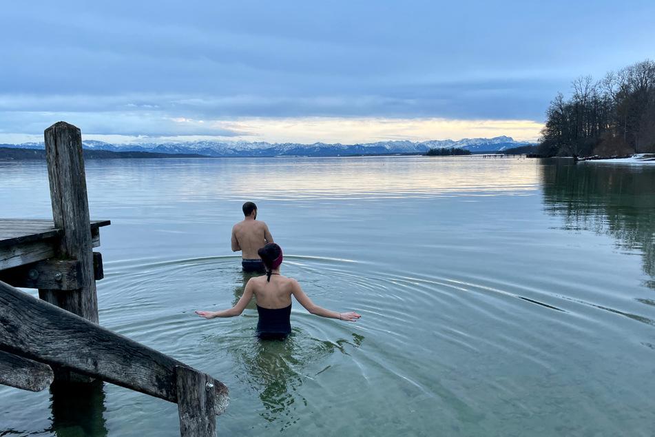 Die Geschwister Tim und Sabrina gehen vor dem Panorama der schneebedeckten bayerischen Alpen im Starnberger See baden.