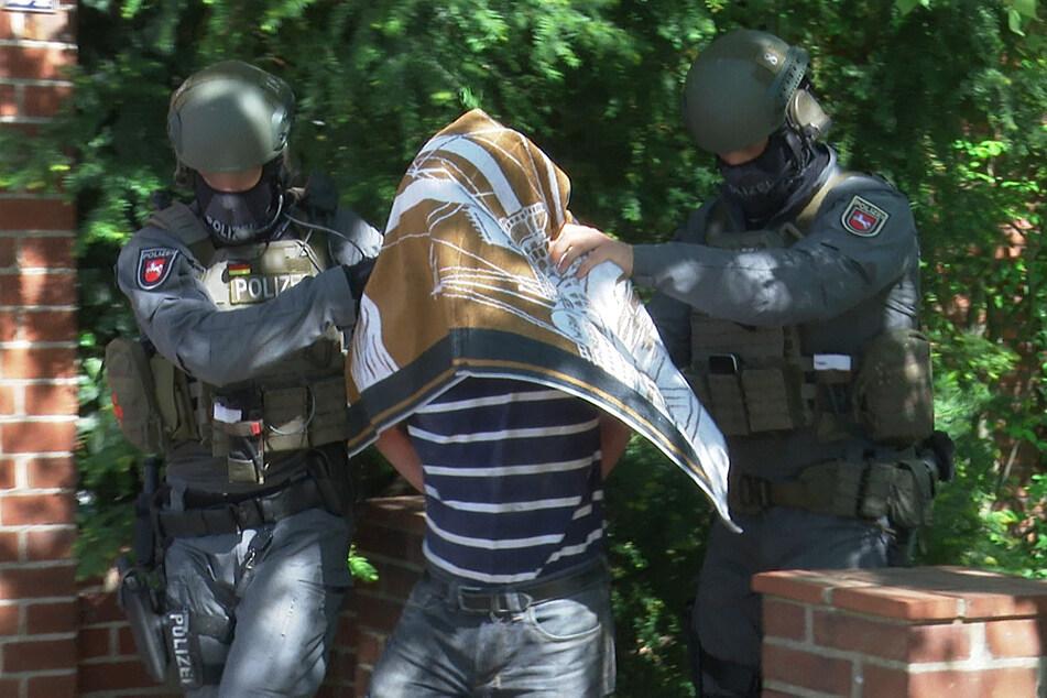 Polizisten führen nach einem Polizeieinsatz den Verdächtigen (53) in Handschellen ab.