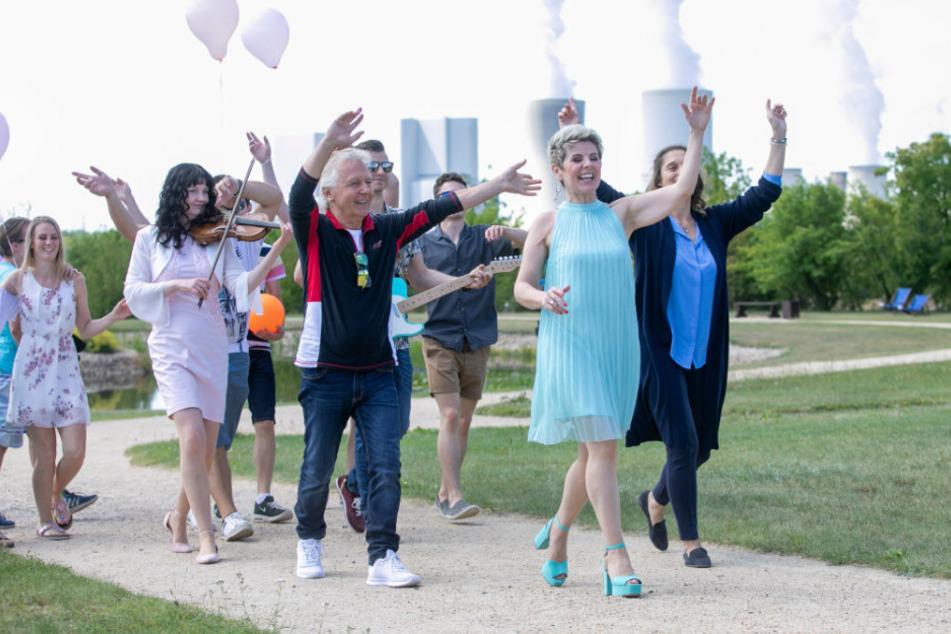 Linda Feller singt sich durch den Findlingspark. Links neben ihr Show-Kollege Muck, dahinter viele Komparsen mit Luftballons.