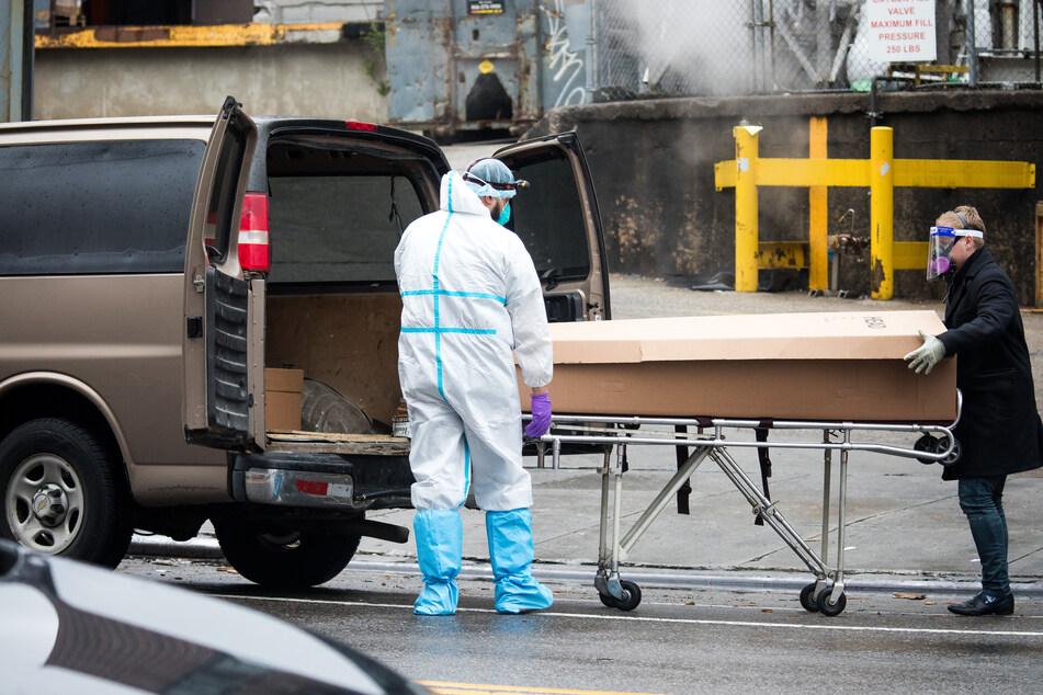 Ein Krankenhausmitarbeiter hilft einem Mitarbeiter eines Bestattungsunternehmens dabei, die Leiche eines an den Folgen von Covid-19 Verstorbenen in einen Kleinbus zu schieben (Symbolbild).