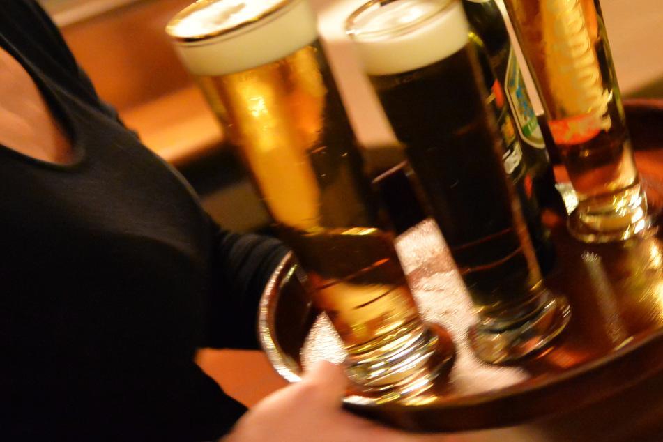 Eine Bedienung trägt in einem Lokal ein Tablett mit Bier – im Corona-Lockdown haben bisher Dutzende Wirte in Hessen gegen Auflagen verstoßen (Symbolbild).