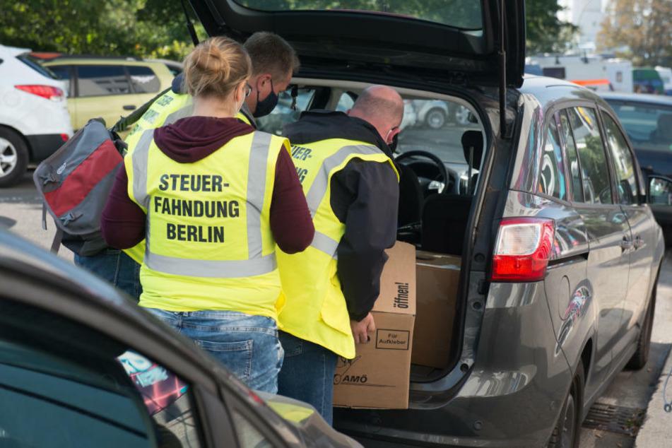 Beamte der Steuerfahndung verstauen Beweismaterial im Kofferraum eines Autos, das sie im Rahmen einer Durchsuchung in einem Geschäftshaus im Bezirk Treptow sichergestellt haben.