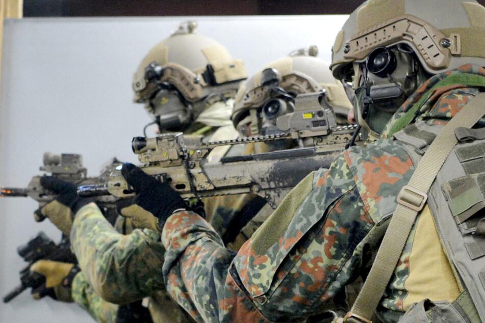 Soldaten trainieren mit Gewehren auf einem Gelände.