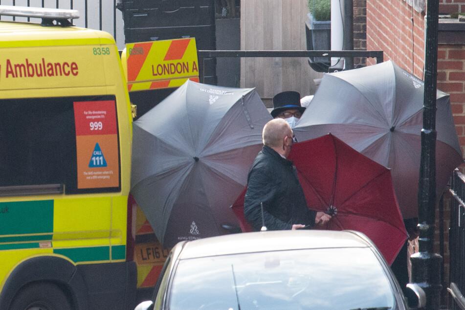 """Mitarbeiter verdecken mit Regenschirmen einen Hinterausgang des """"King Edward VII Krankenhauses"""", in dem der britische Prinz Philip seit dem 16. Februar behandelt wurde."""