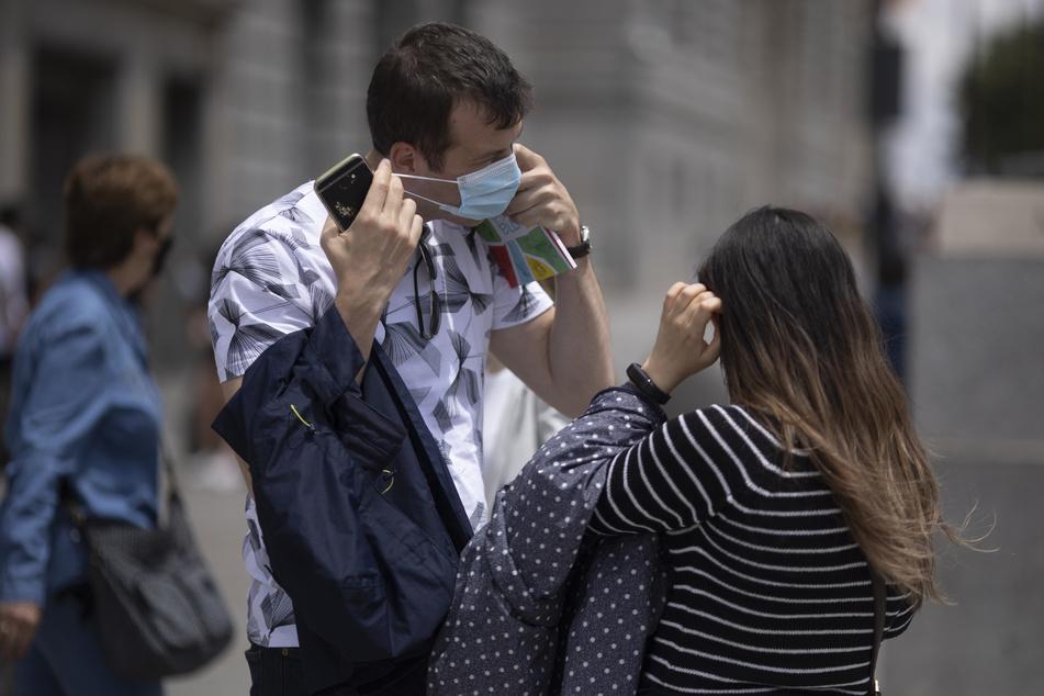 Ein Mann nimmt an der Puerta del Sol seine Maske ab. Die Maskenpflicht wird in Spanien ab Samstag erheblich gelockert.