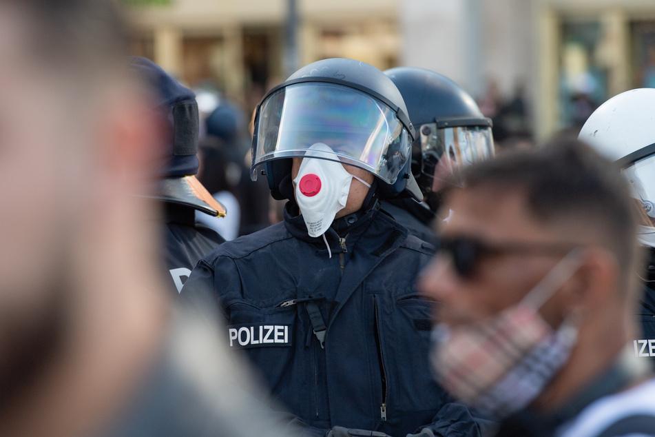 Ein Polizist mit einer Atemschutzmaske steht am Rande einer Demonstration.