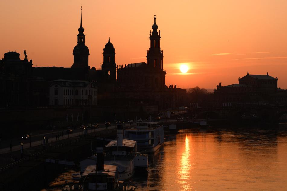 Der Hausmannsturm, das Ständehaus, die Katholische Hofkirche und die Semperoper zeichnen sich vor der untergehenden Sonne am Ufer der Elbe als Silhouetten ab.