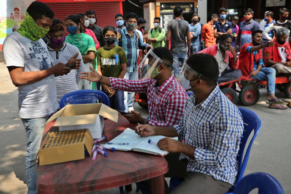 Bengaluru, Indien: Reisende registrieren sich vor einem Bahnhof, um einen Corona-Test zu machen.