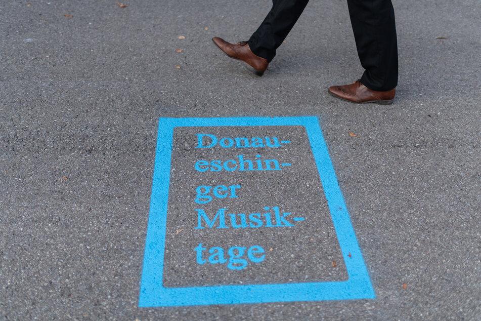Ein Mann läuft am Logo der Donaueschinger Musiktage vor der Donauhalle vorbei.