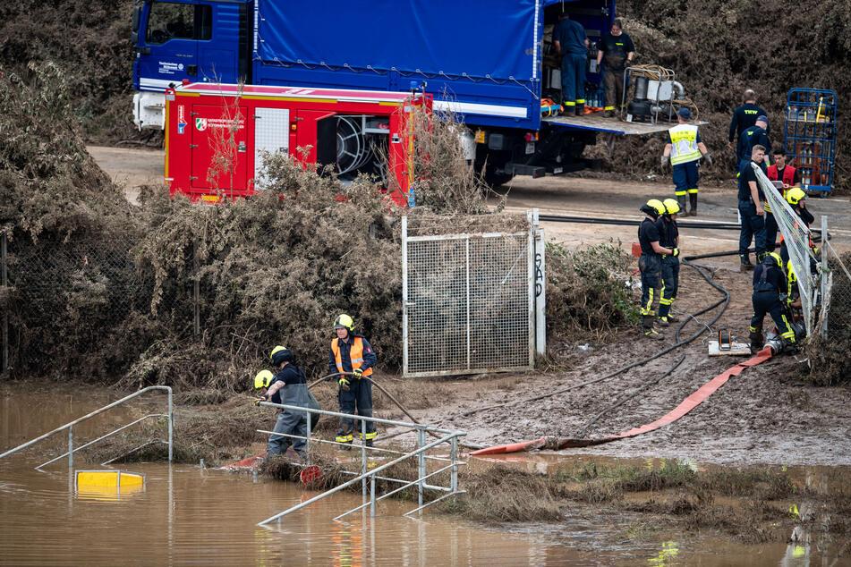 In Erftstadt pumpen Helfer von Feuerwehr und Technischem Hilfswerk (THW) Wasser aus einem Regenrückhaltebecken ab, in dem sich noch Fahrzeuge befinden sollen.