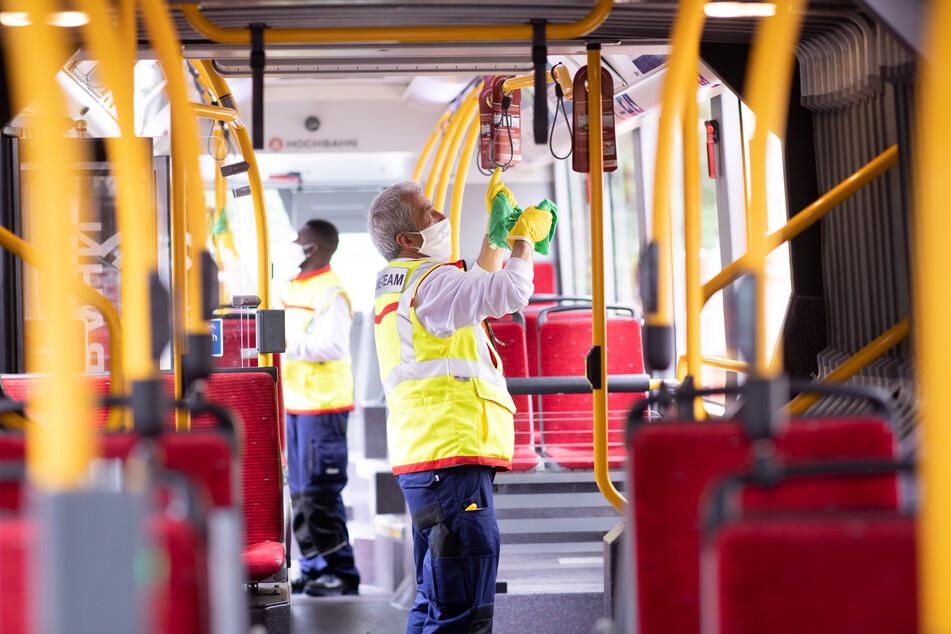 Mehmet Ince (r) und Abdul Razak Alidu, Mitarbeiter eines Hygieneteams von Tereg für die Hamburger Hochbahn, arbeiten in einem Gelenkbus während einer Standpause am Bahnhof Altona.