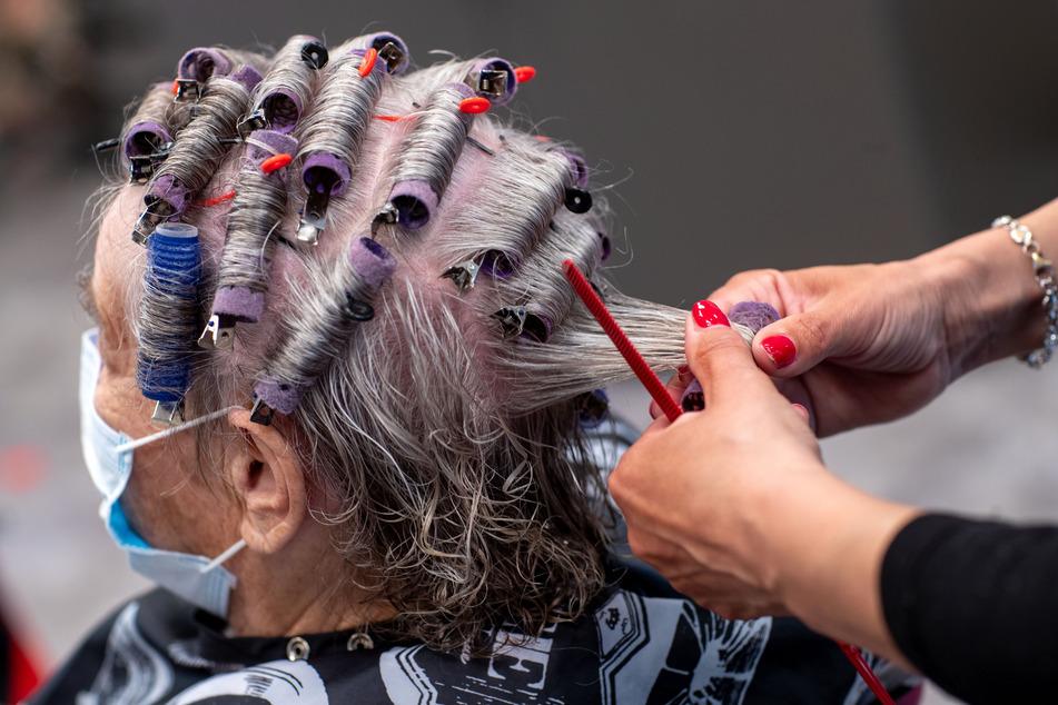 Einer Kundin werden in einem Friseursalon die Haare frisiert (Symbolbild).