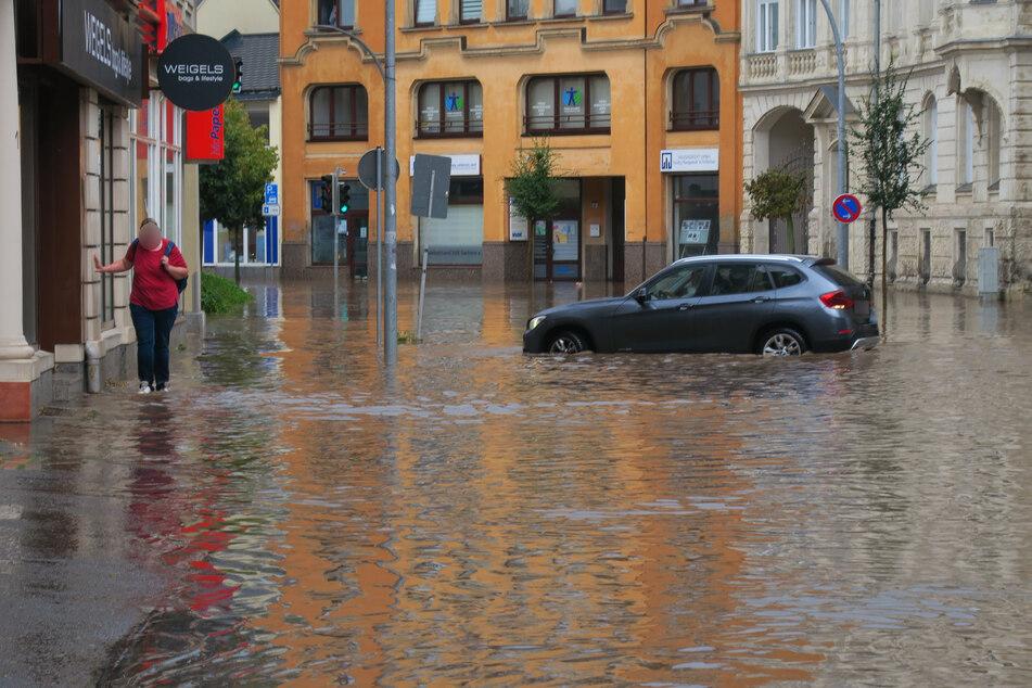 Die Bahnhofsstraße in Aue: Ein BMW steckt in einer riesigen Pfütze fest. Innerhalb von Minuten verwandelte sich die Straße in einen kleinen See.